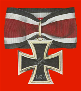 A silver framed black cross that has arms which are narrow at the center, and broader at the perimeter. In the middle of the cross is a swastika, an equilateral cross with its arms bent at right angles. On the lower arm of the cross are the number 1939 engraved. The cross is connected to a ribbon with a silver clip. The ribbon has a red central stripe, flanked in white and with a black edge stripe.