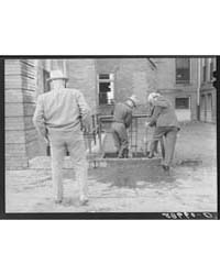 Men Cleaning Their Boots After Visit to ... by Library of Congress