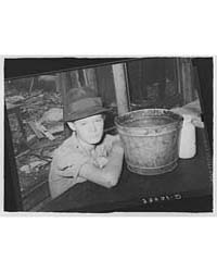 Boy Sitting at Table in His Shack Home N... by Library of Congress