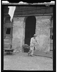 Man Cleaning Out a Small Building, New O... by Genthe, Arnold
